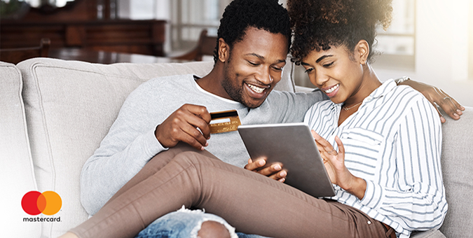 happy couple on couch making purchase with their SMB debit card